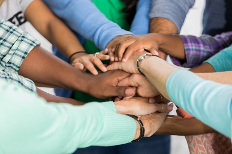 Diverse group of people put hands together in team building exercise. View is of hands and arms only.